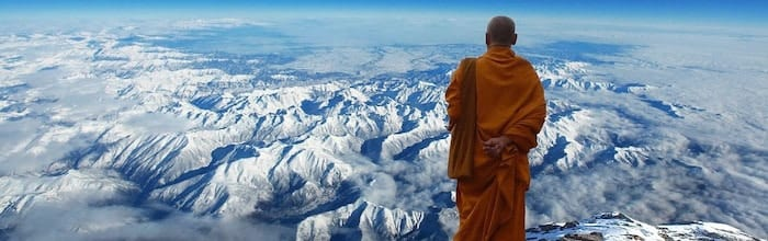 A Buddhist monk gazes out at the mountains