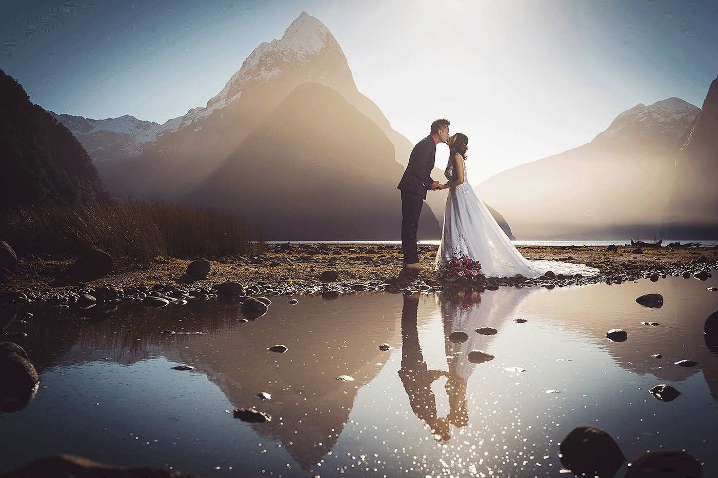 A groom kisses his bride at sunset in front of Mitre Peak during a Milford Sound pre-wedding shoot - Fallon Photography