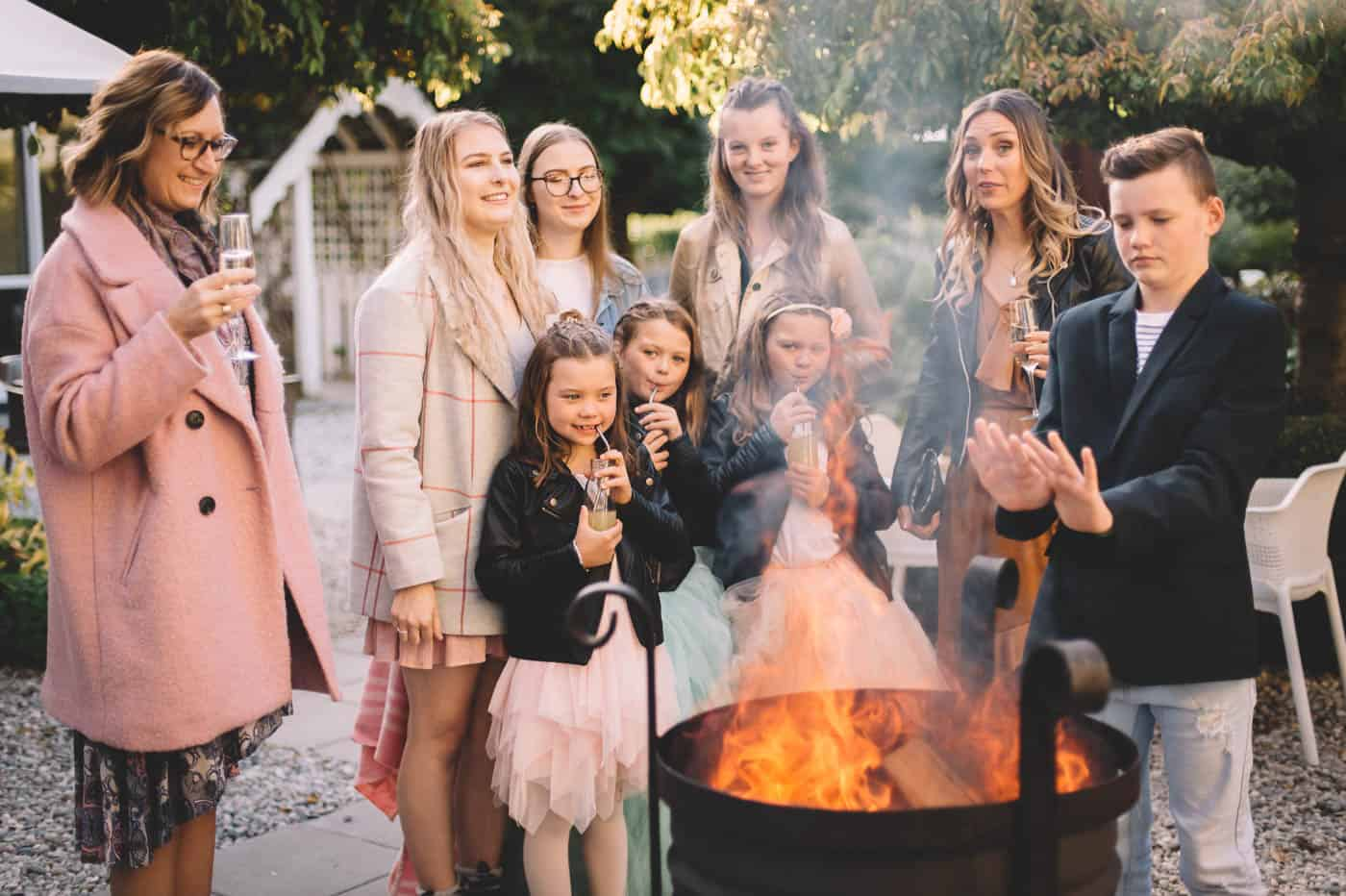 blog post featured image Sam and Kirk and family warm their hands over a fire at Akarua Wines and Kitchen by Artisan during their wedding reception